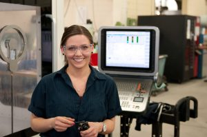 Female CNC Machinist wearing safety glasses